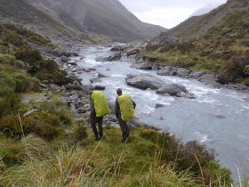 Two hikers walking along a stream in New Zealand.