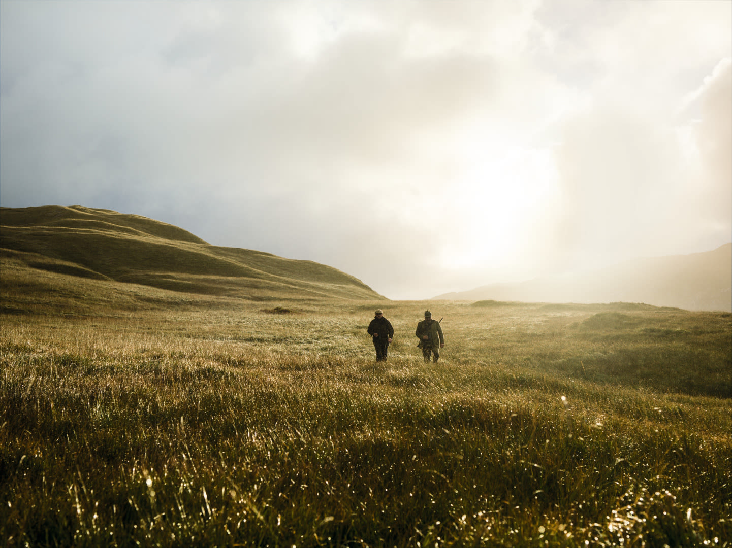 Two hunters walking on a field with a Swarovski Optik dS rifle scope