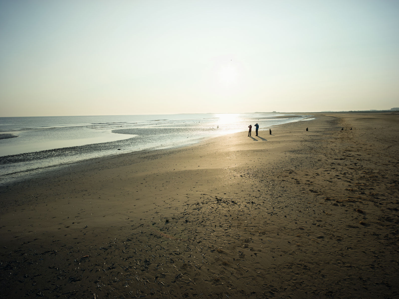 Beach with two people walking very far away, England