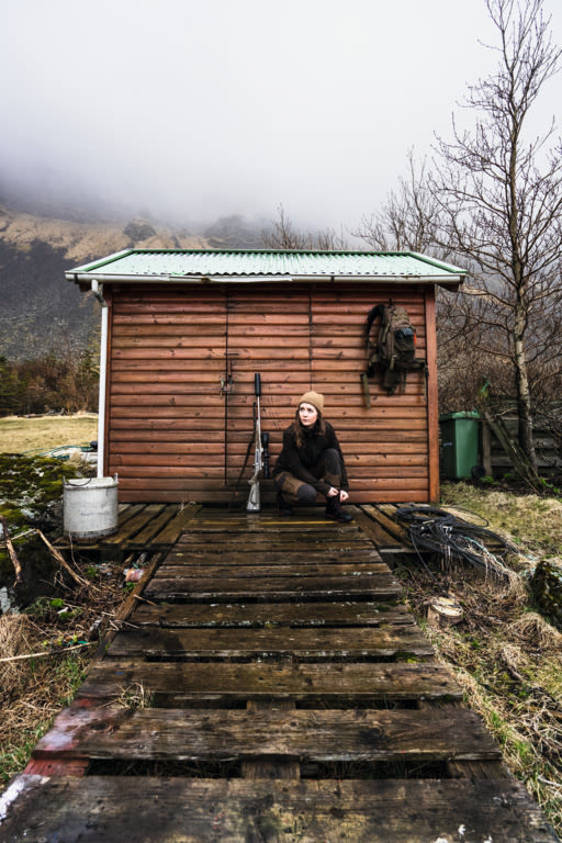 Iceland Hunters Alma sitting infront of a hut