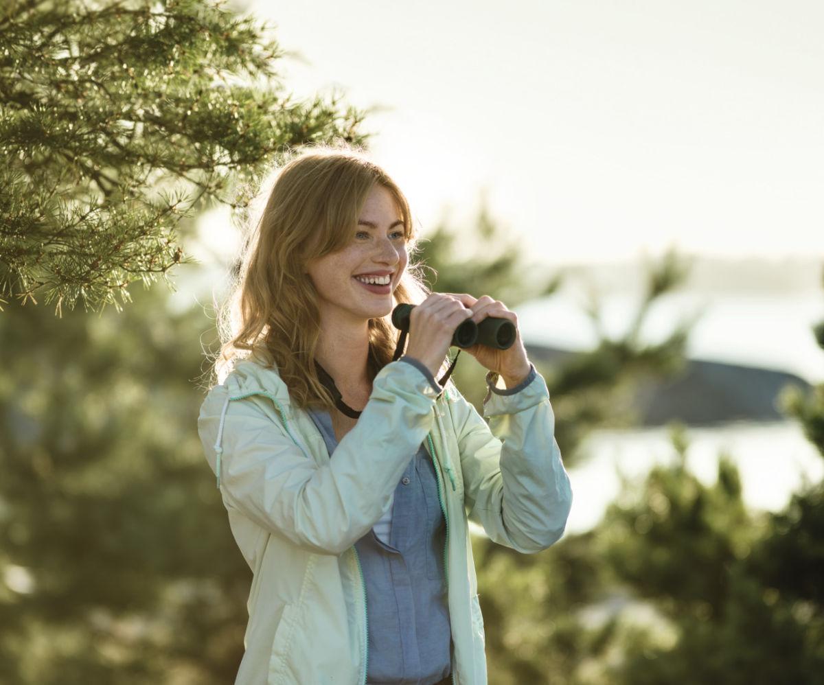 CL Companion 2017 woman with binoculars at lake ID 1037143