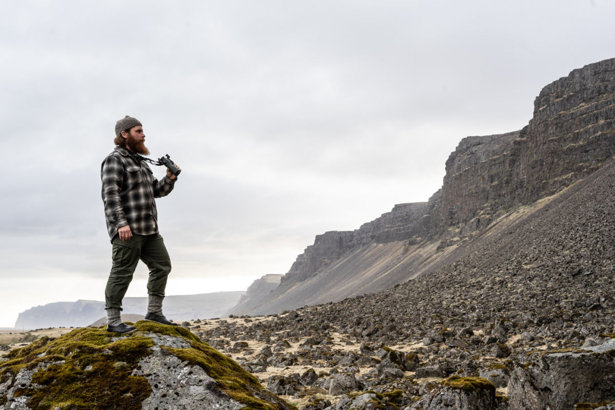 One with nature: the Iceland Hunters stalking with the NL Pure - Gunnar from hunting_iceland standing on a rock with the SWAROVSKI OPTIK NL Pure with FRP forehead rest rocky landscape