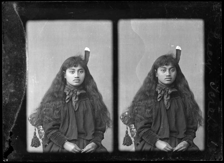 Stereoscopic image of a woman sitting for a portrait with a huia feather in her hair.