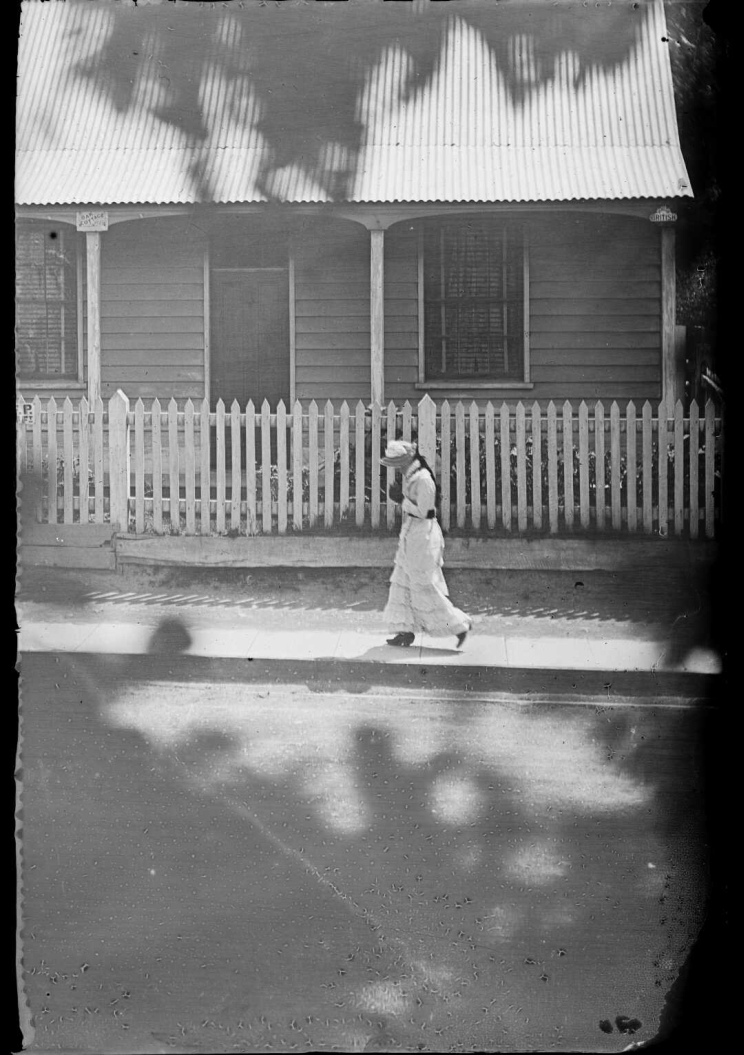 A woman walks on the footpath in front of white picket fence and a wooden house in the background, the ground is dappled in shade from a tree.