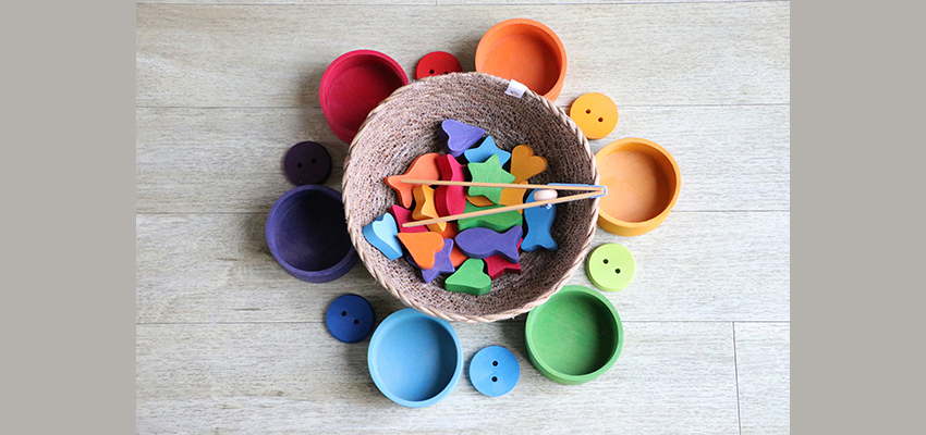 Brightly coloured bowls and buttons around a basket containing different coloured shapes (fish, stars, hearts) and 2 sticks