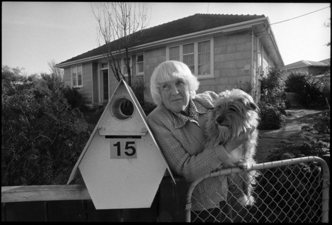 Mrs Zeta Tutt standing at the gate of her State house with her dog Benji, Naenae - Photograph taken by Phil Reid. Dominion post (Newspaper) :Photographic negatives and prints of the Evening Post and Dominion newspapers. Ref: EP/1992/3218/35