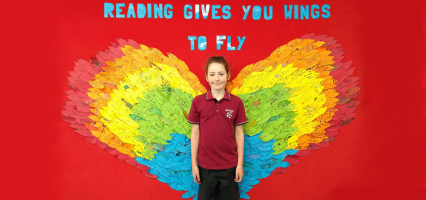 Student in front of a display of wings and with the words 'Reading gives you wings to fly'