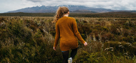 Tongariro peak shrouded in clouds in the background with a girl in brown jersey stepping towards the mountain in the foreground