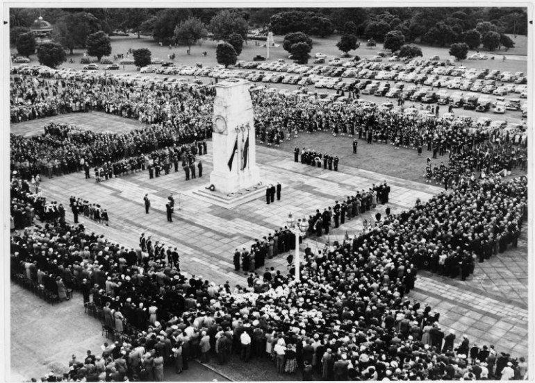 Anzac Day service, showing crowds gathered at a memorial.