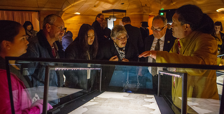 Visitors looking at Te Tiriti o Waitangi at the He Tohu exhibition opening.