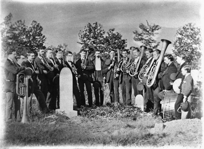 Members of a brass band gathered around a grave, ca.1890s.