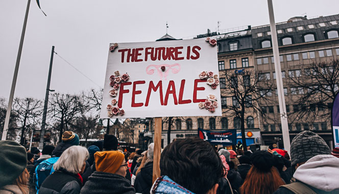 Women protesting and one holding a banner saying 'The future is female'.
