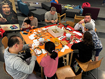 Group of people sitting around a table making taonga pūoro.