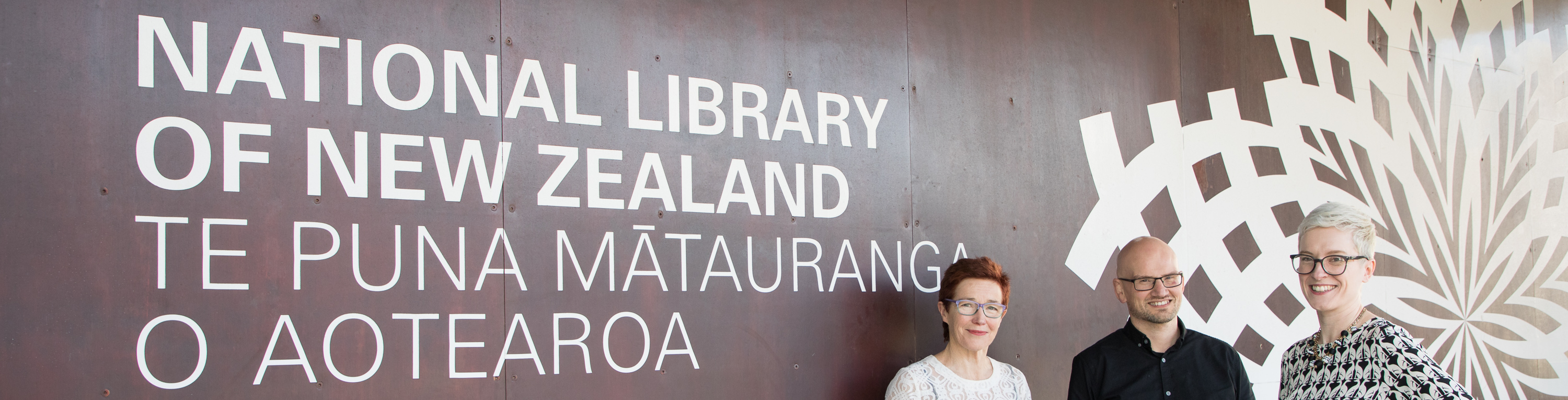 Two women and one man standing in front of a sign that reads National Library of New Zealand Te Puna Mātauranga o Aotearoa.