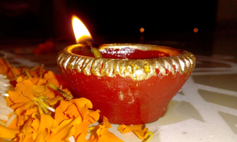 Burning Diwali candle and yellow flower petals