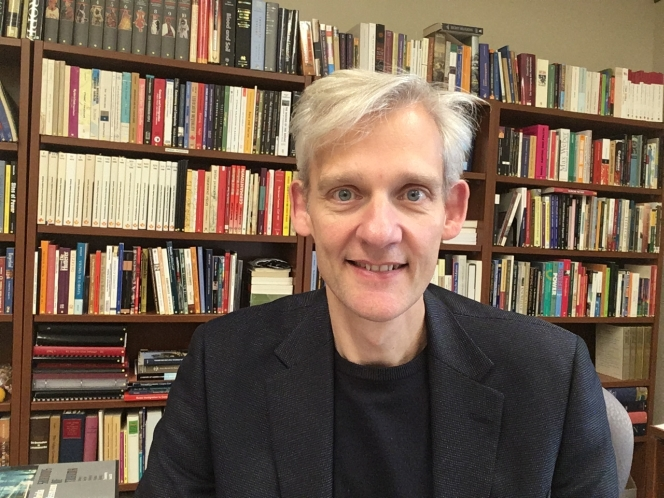 A portrait of Professor Alexander Freund in a study with bookshelf in background.