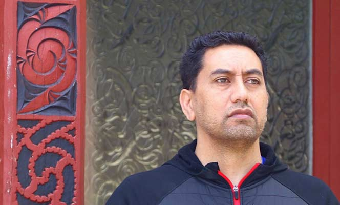 Nepia Mahuika standing next to a Māori carving