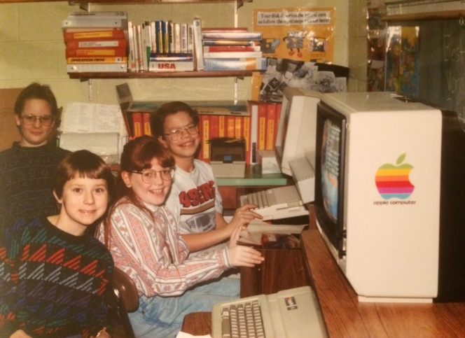 The author (pictured centre) at a Macintosh computer in her primary school. Photographer unknown.