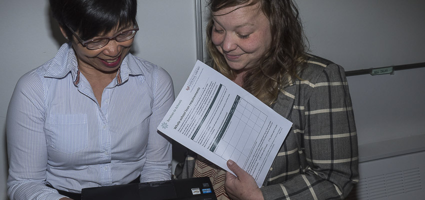 Two people smiling one with a loan form looking at a laptop.