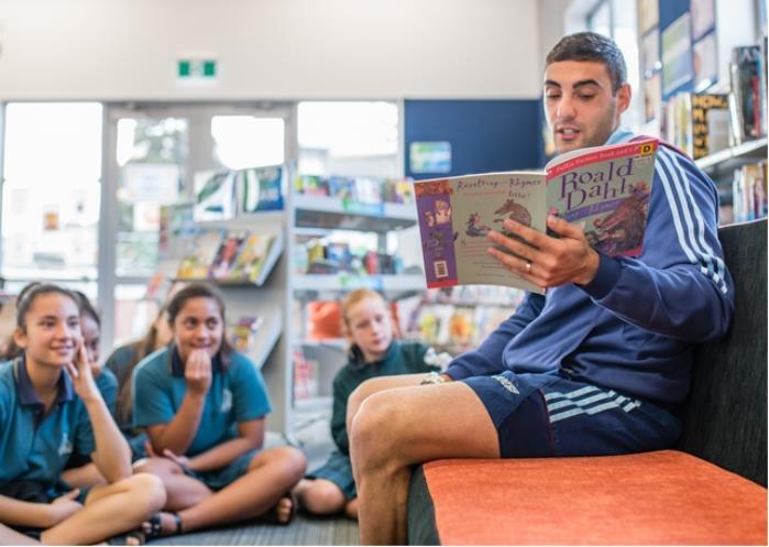 Dan Bowden reading a Roald Dahl Book to children.