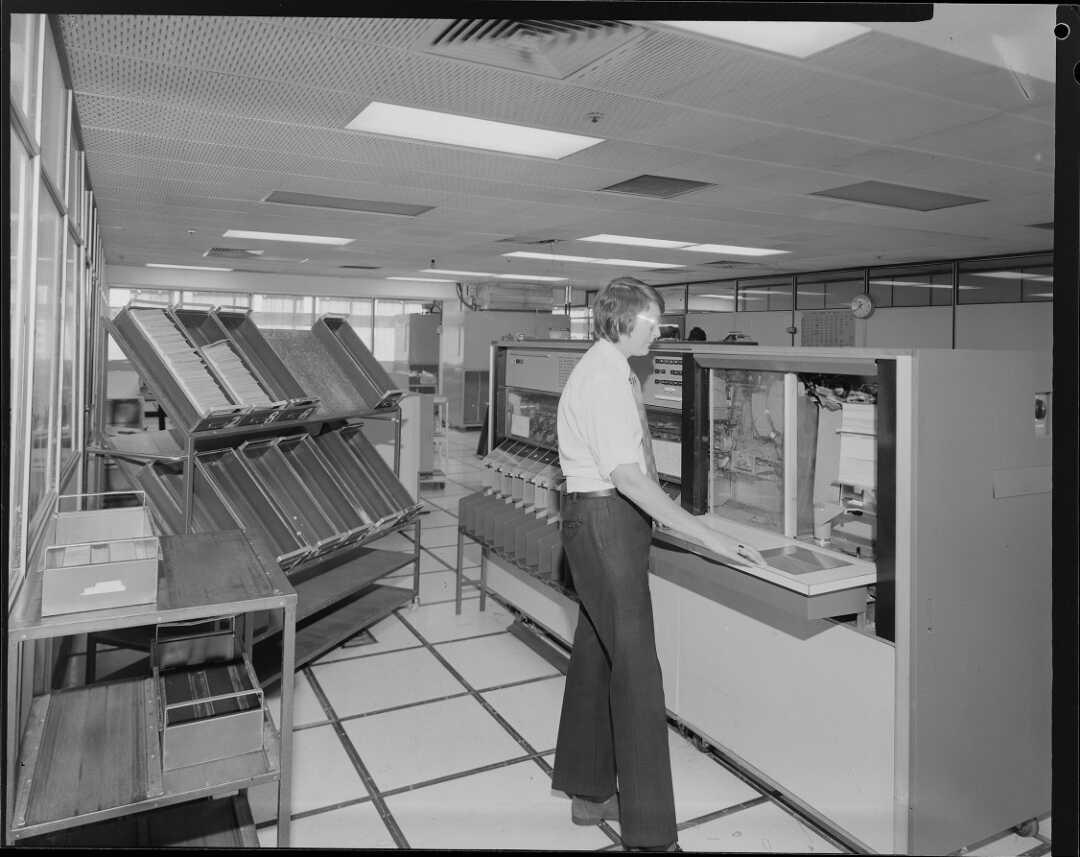 Man operating large computer, 1975.