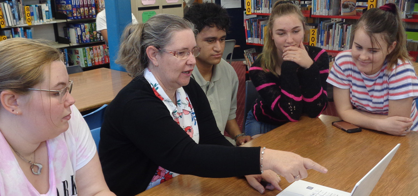 Librarian and 4 students in the school library, looking at a computer screen