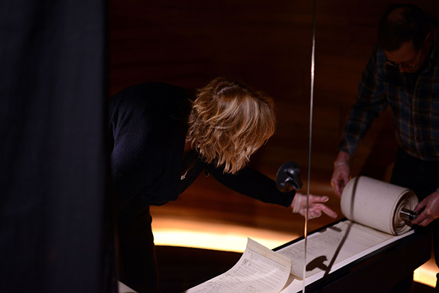 Conservator turning the Women's Suffrage Petition scroll