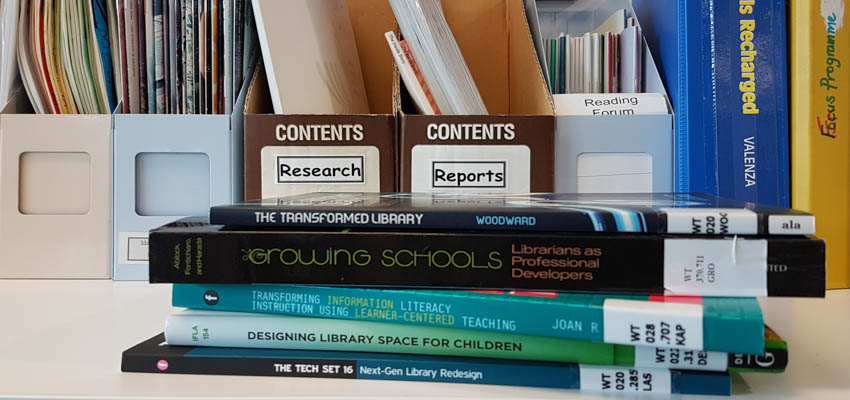 Desk with books on library trends and research.