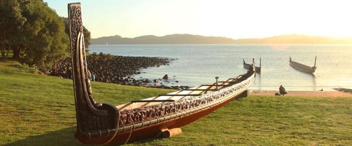 Carved Māori waka on beach with water and waka in background