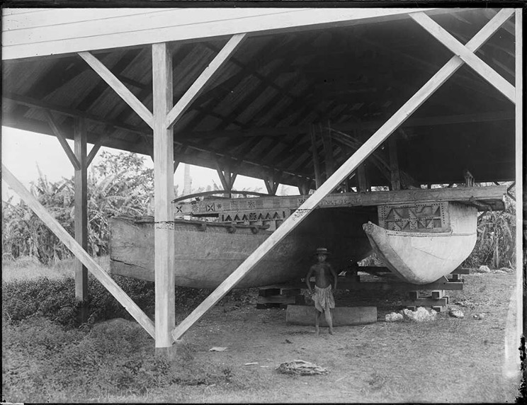 Boy standing in front of a big double hull canoe.