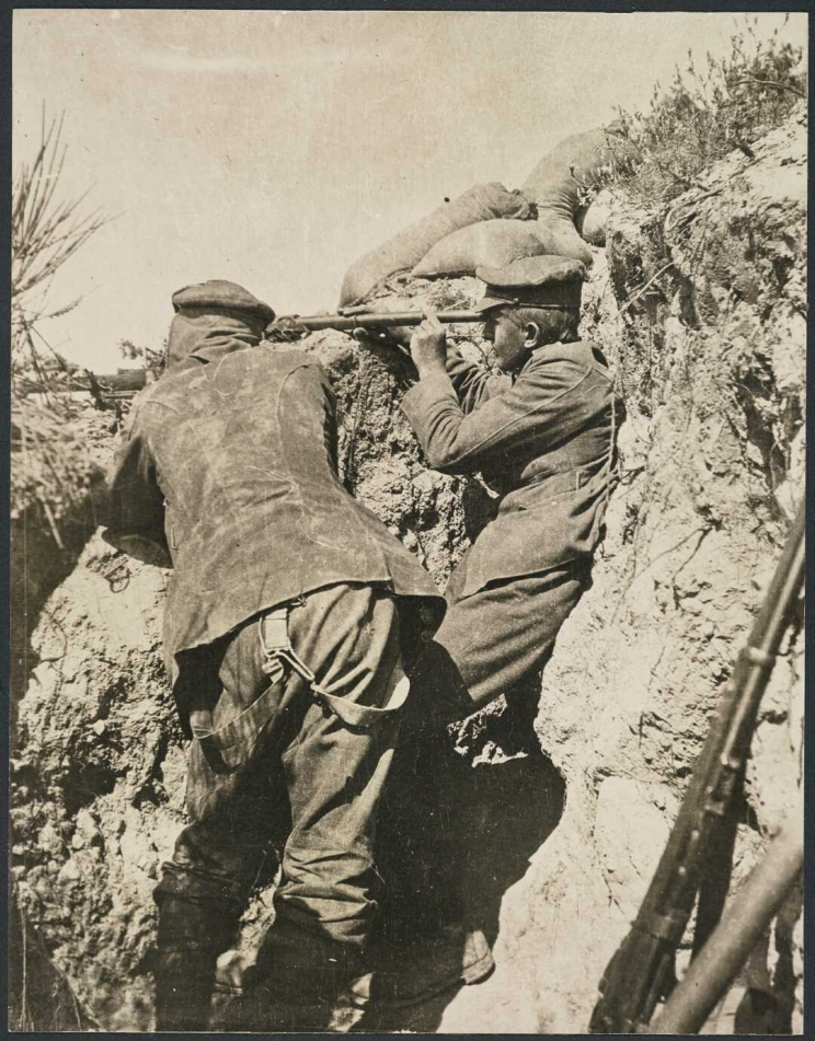 Two soldiers in a trench, one is looking through a telescope while the other the aims a rifle.