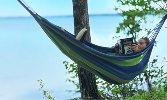 Girl reading 'Diary of a Wimpy Kid' paperback while lounging in hammock by the sea