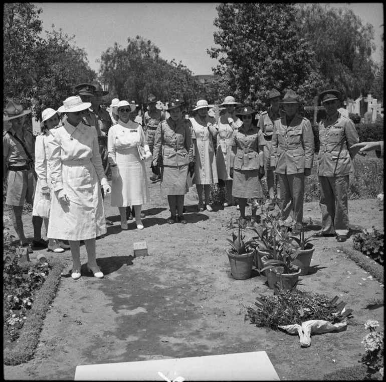 Women and men wearing white and khaki uniforms stand at the cemetery.
