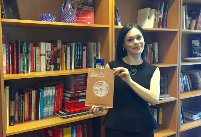 Tui Dewes at the embassy library with a copy of the Turnbull Library Record.