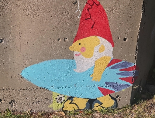 A gnome wearing a red hat and holding a surfboard has been painted on a concrete wall.