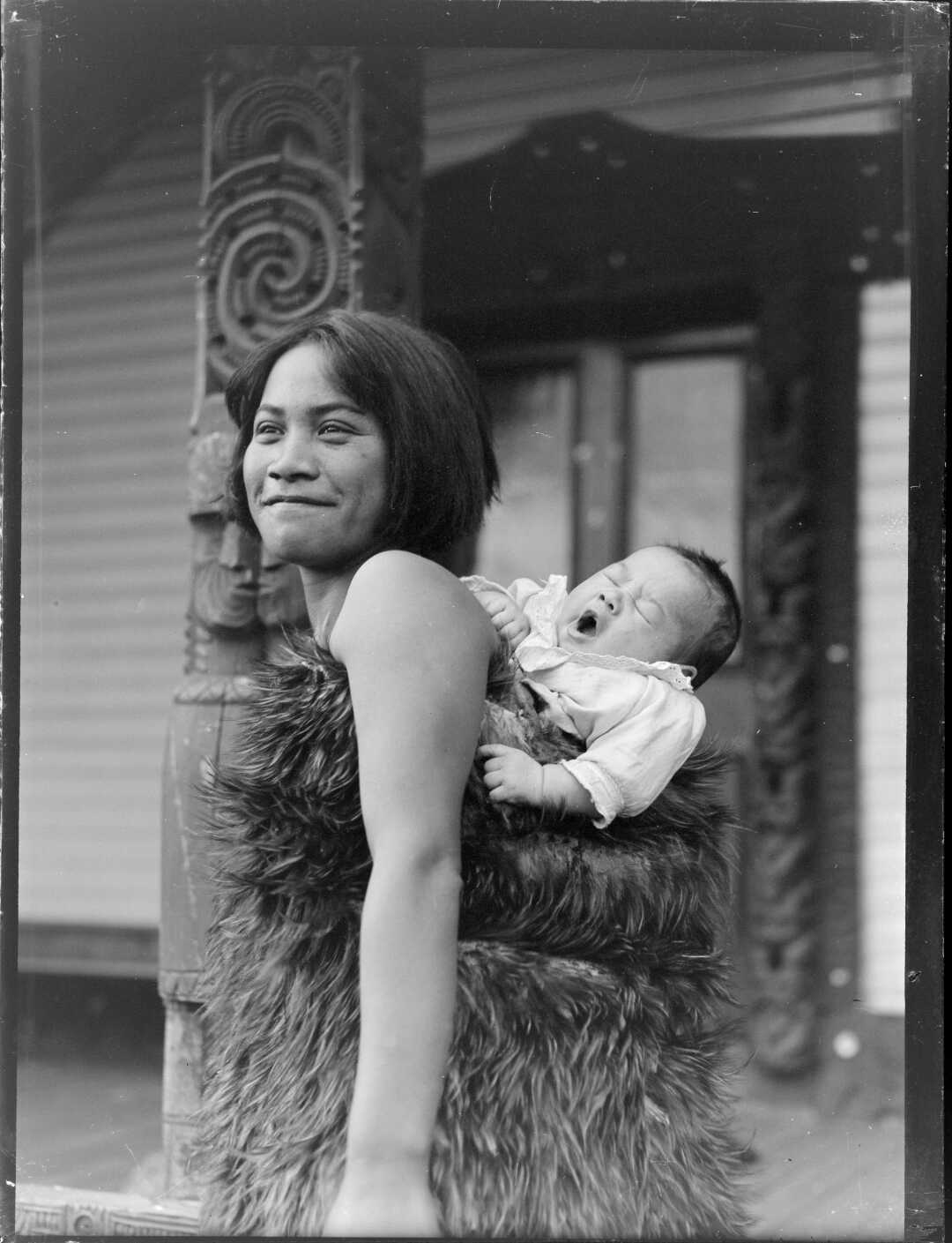 Maori woman carrying a young child on her back wrapped in a feather cloak. Ref: WA-12537-G