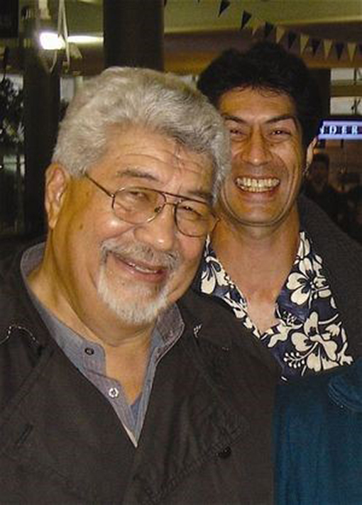 Headshot of an older man and younger man smiling at the camera.