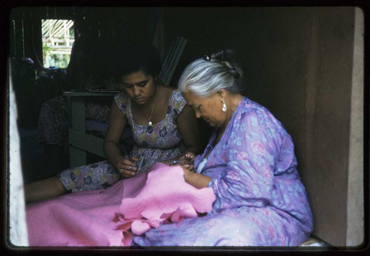 Two women sitting on the ground sewing.