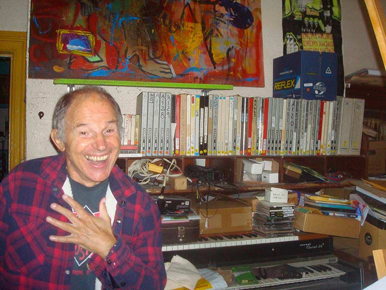 A smiling Chris Knox in front of keyboards and tapes.