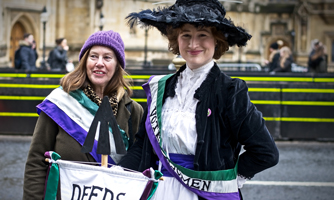 2 women, one dressed as a suffragette, wearing sashes with words 'Votes for women' and holding a banner 'Deeds not words'