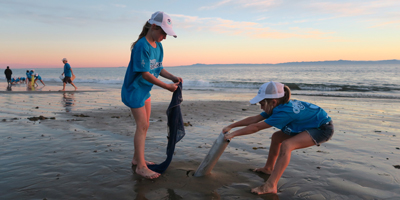Two primary school students on a beach participating in a science project using ocean research equipment on the sand at sunset with water and other figures in the background