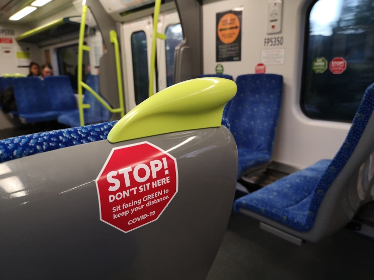 Sticker for seat back in the shape of a red stop sign for public buses and trains to maintain social distancing.