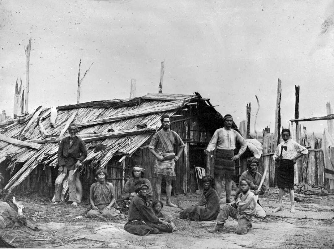 Shows both men and women standing and seated in front of a wooden whare.