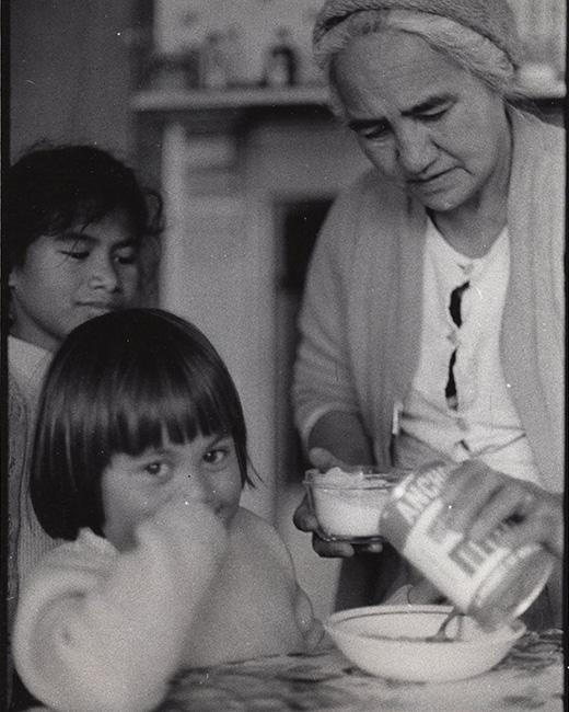 Two young children watch as a kuia pours evaporated milk on a plate of kānga waru.  [Kanga waru](/files/schools/hm46-kanga-waru-english.mp3)