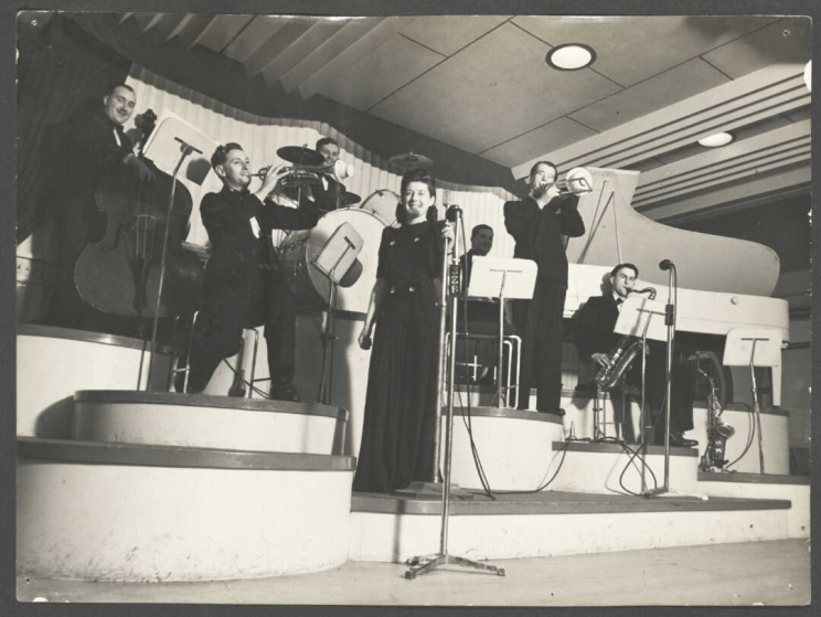 Black and white photo shows Lauri Paddi on stage with her band behind her, playing their instruments.
