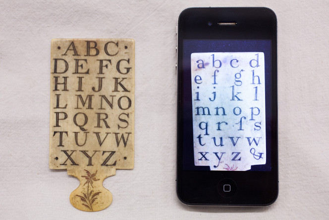 Hornbook showing uppercase alphabet, next to a cellphone. The cellphone is showing the reverse side with lowercase letters.