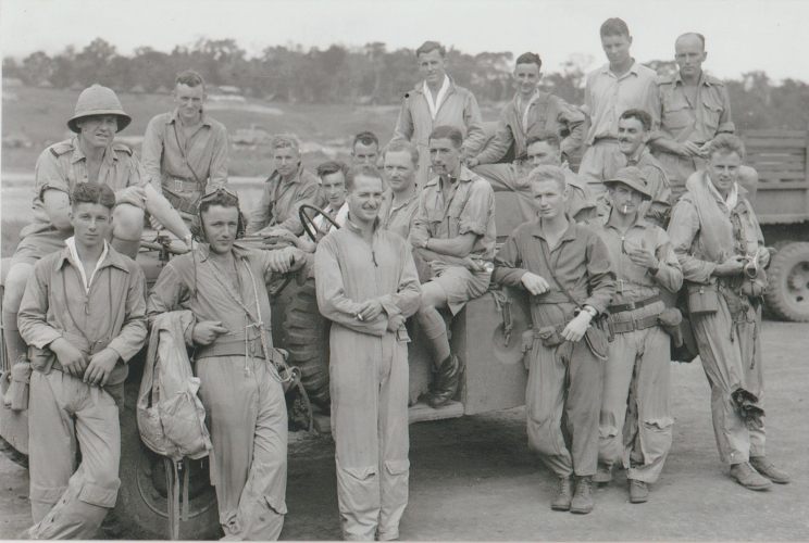 A group of men in military uniform standing and sitting in a jeep all smiling and looking at the camera.