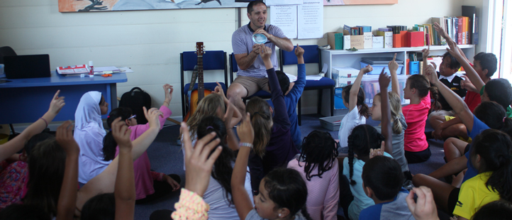 Teacher holding up an inquiry resource (a paua shell) to a class of students with their hands up