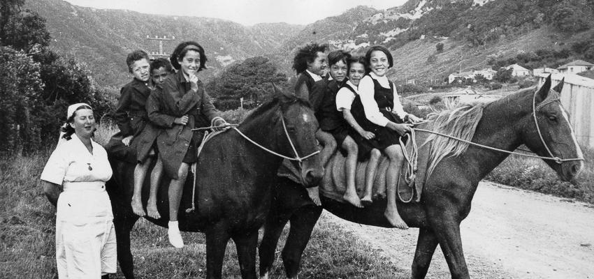 Seven Maori children on two horses beside a pakeha dental nurse.