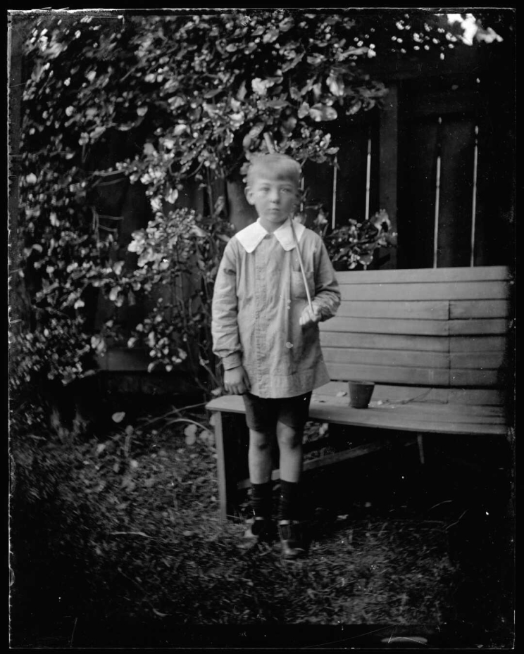 A boy stands beside a bench holding a slim stick over his shoulder as if it were a rifle.